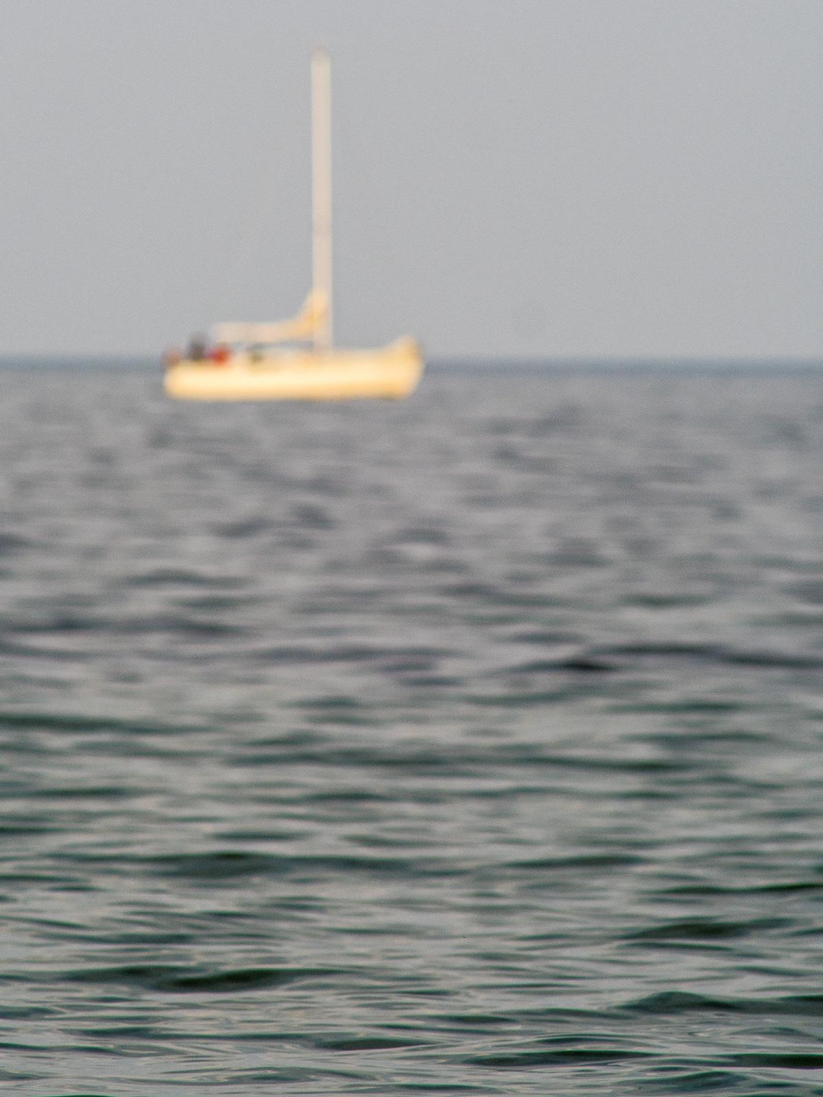 unscharfes Segelboot mit Wasser im Vordergrund