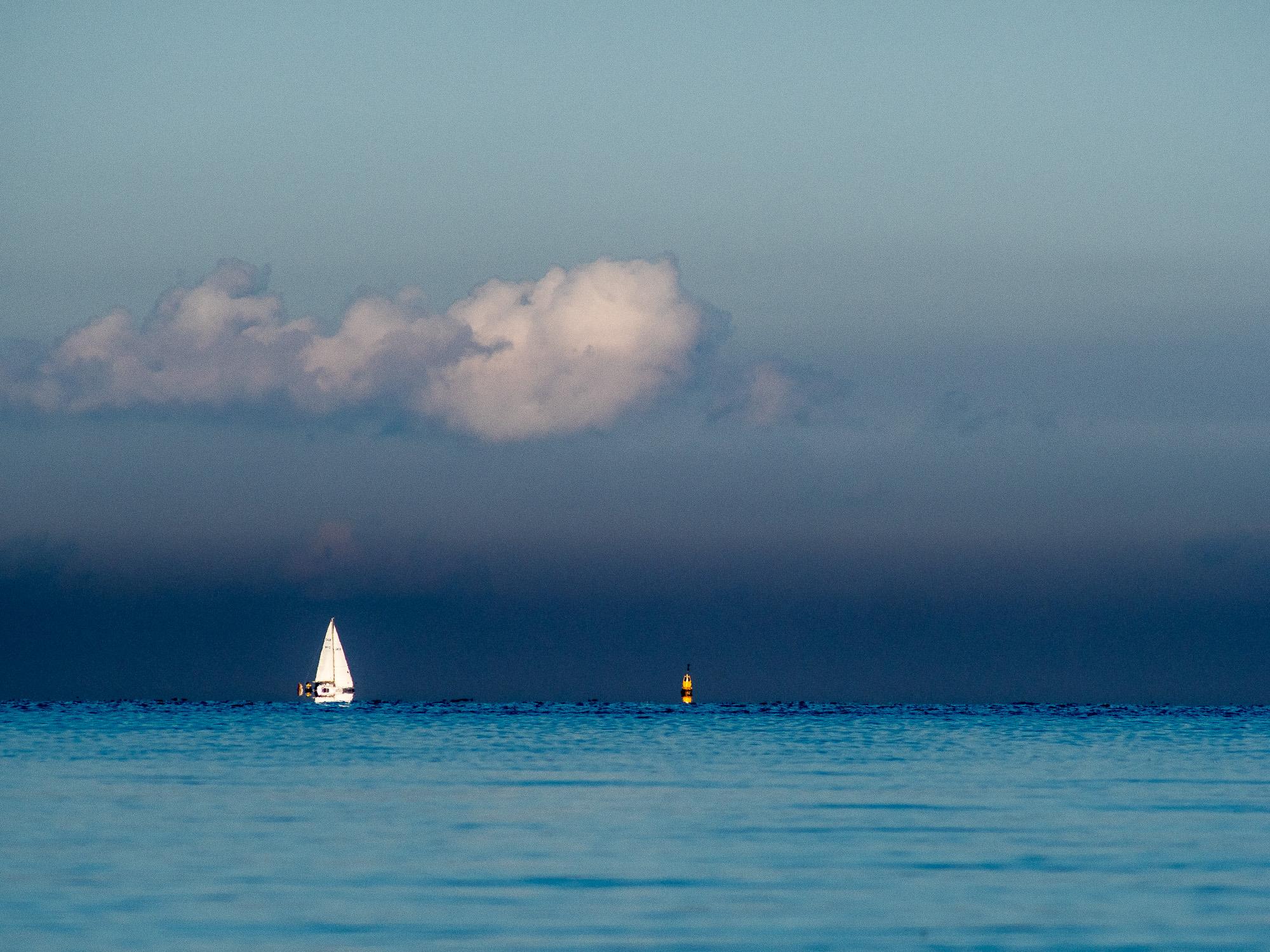 Segelboot und Boje unter dramatischer Wolke