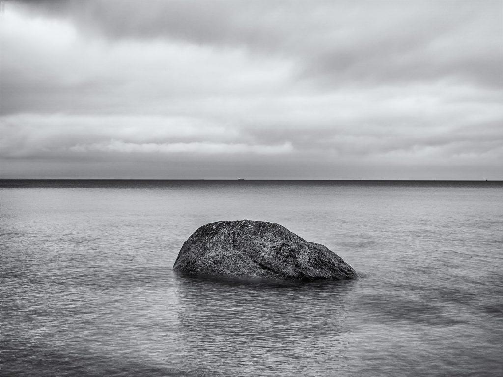 Felsen im Wasser, dichte Wolken, schwarzweiß