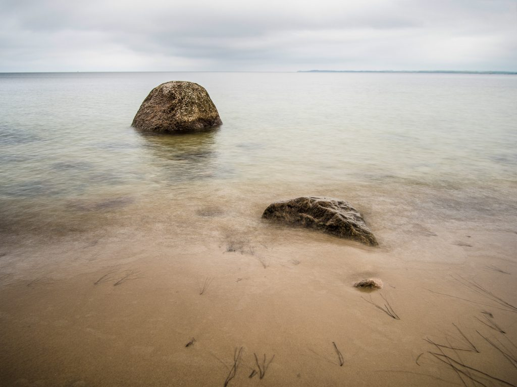 Ein Felsen im Wasser, einer an der Wasserlinie im Sand