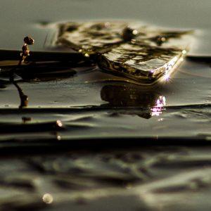 Lichtreflex in einem Stückchen Eis auf einer dünn überfrorenen Pfütze