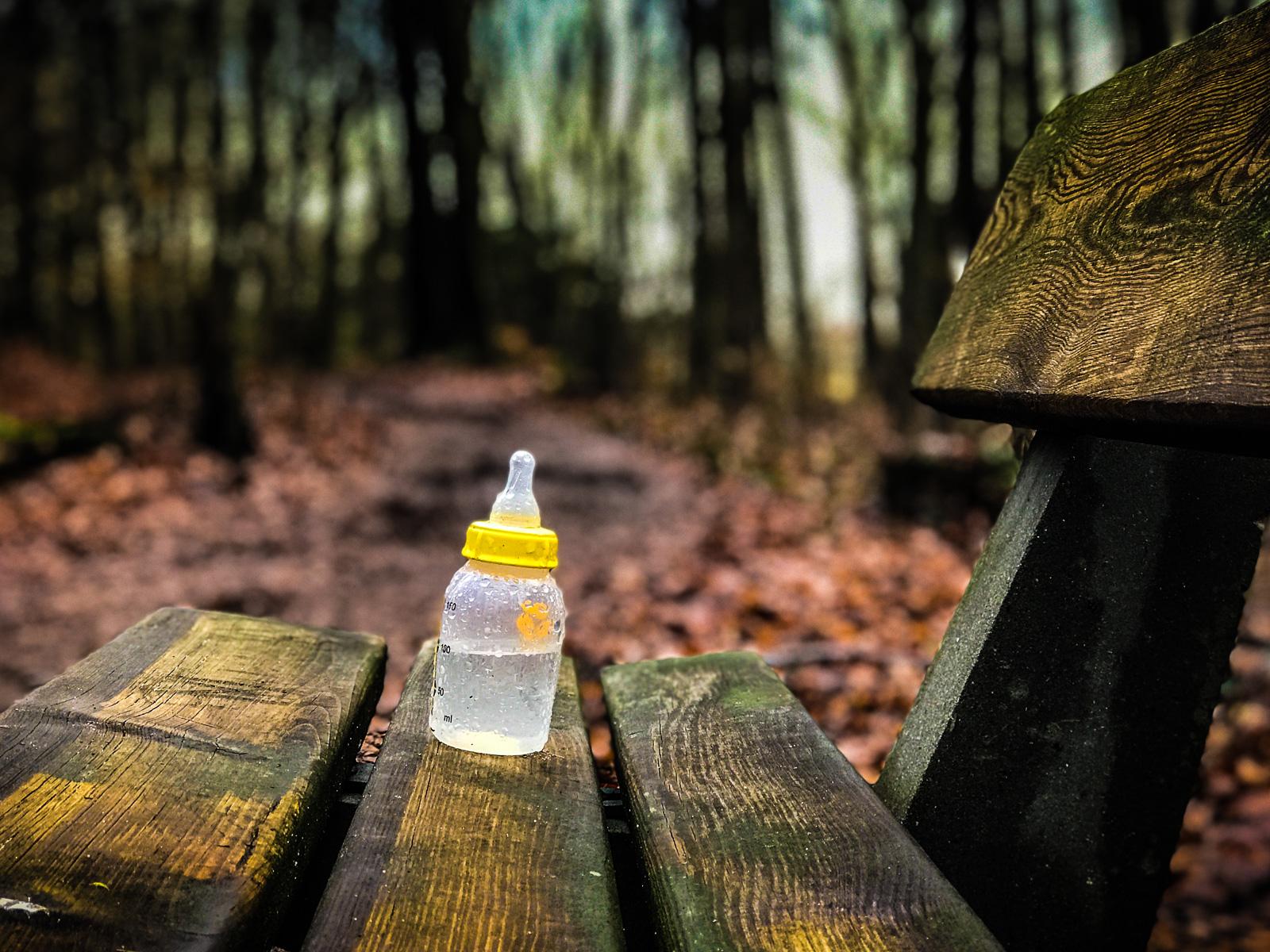 Nuckelflasche auf nasser Bank im Wald