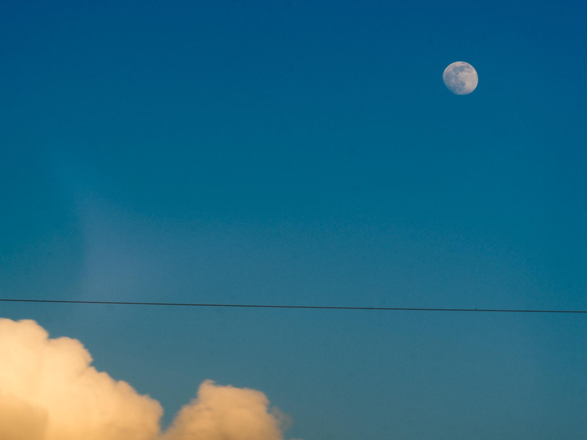 Mond am noch blauen Taghimmel über einem Stromkabel und einer angeleuchteten Wolke