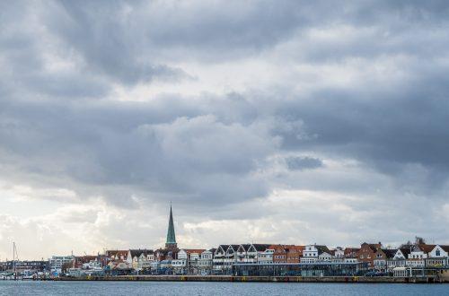 """Die """"Wasserlinie"""" von Travemünde in der Nachmittagssonne unter spektakulären Wolken"""
