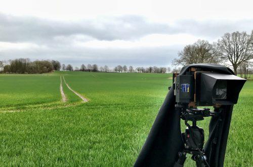 Grünes Feld mit Treckerfahrspur unter grauem Himmel, im Vordergrund meine Holzkamera