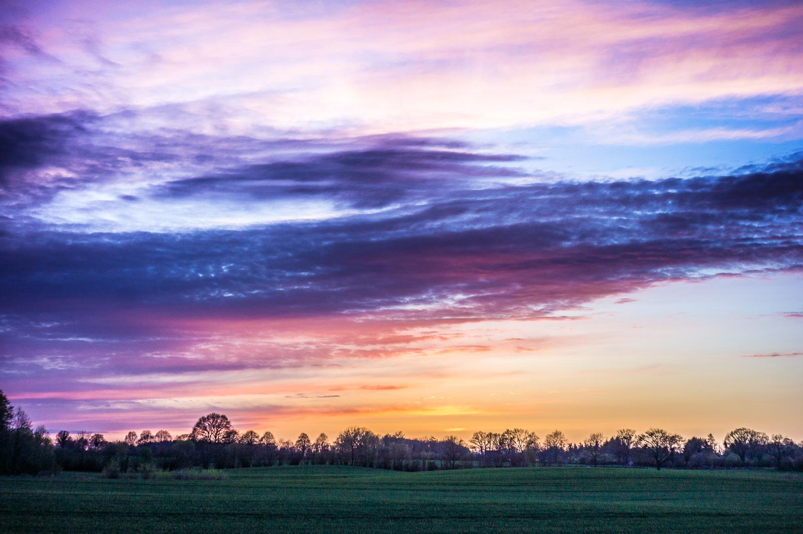 Kitschbunter Sonnenuntergang über der Wiese